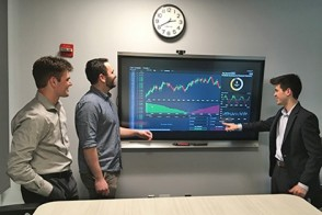 Three students work with a touchscreen to show an investment management platform.