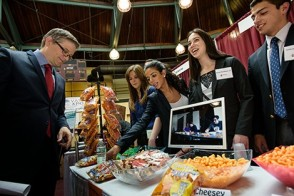 A group of students offer samples of their wares to a professor.