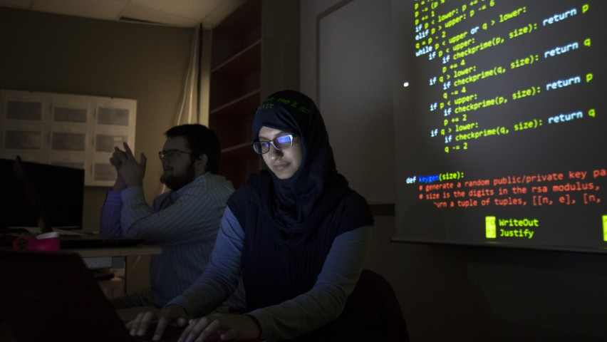 Woman student in classroom with computer code on screen behind her