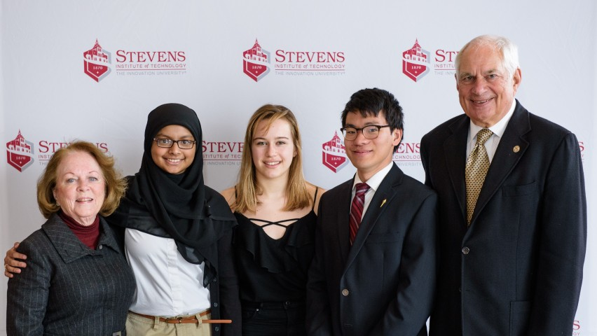 Students and alumni pose in a group of five