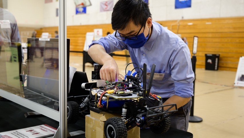 A student wearing a black mask and blue shirt. He is leaning over a robotic vehicle with wheels and adjusting some components on the top of it.