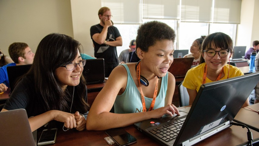 Three female students in front of a laptop in a pre-college classroom