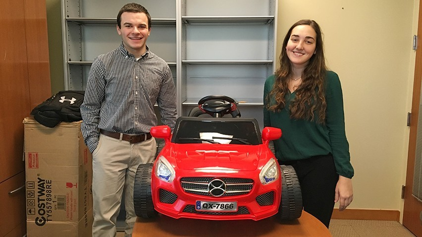 A male and female student in a Stevens office, standing with a red toy car they rewired for students with disabilities.