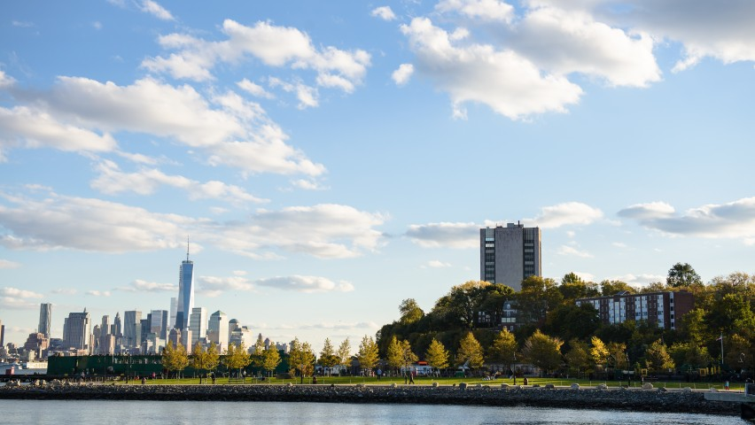 Image of Stevens campus and New York skyline on the horizon under blue sky and white clouds