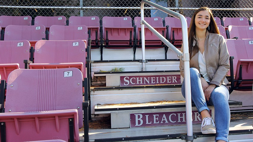Undergraduate business student Zenya Koprowski sitting on the Schneider Bleachers.