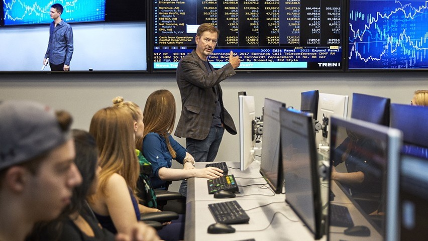 George Calhoun, in a checked jacket, gestures to Bloomberg data on a large screen as he teaches a class in the Hanlon lab.