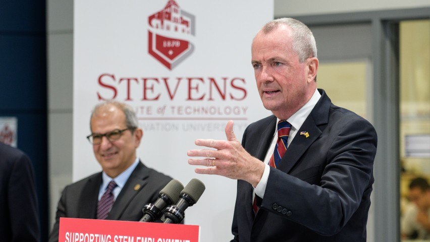 Gov. Phil Murphy speaking at the podium in the ABS  Engineering Center at Stevens Institute of Technology as President Nariman Farvardin looks on