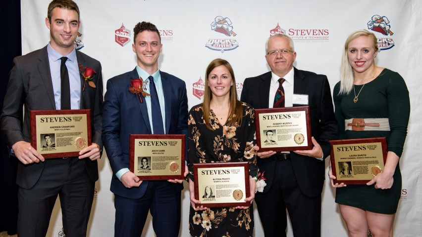 Five alumni athletes hold plaques commemorating their membership in the Stevens Athletics Hall of Fame.