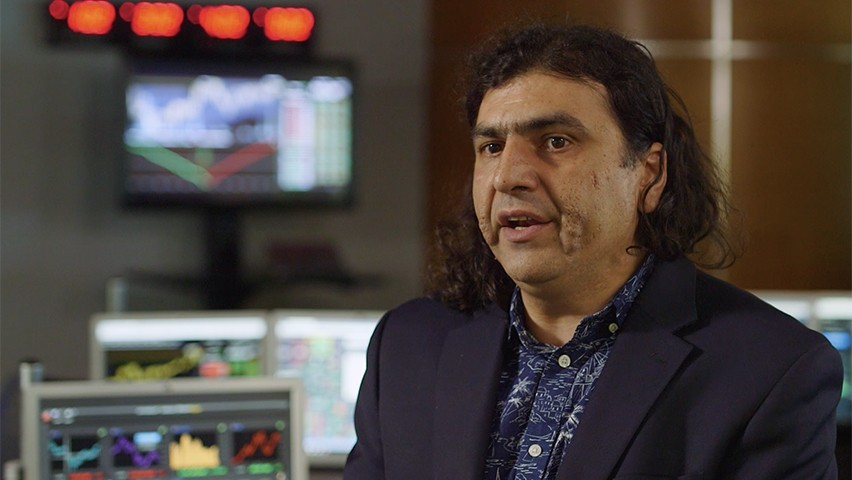 Ionut Florescu, in a dark shirt and jacket, speaking in the Hanlon Lab. Bloomberg terminals are visible in the background.