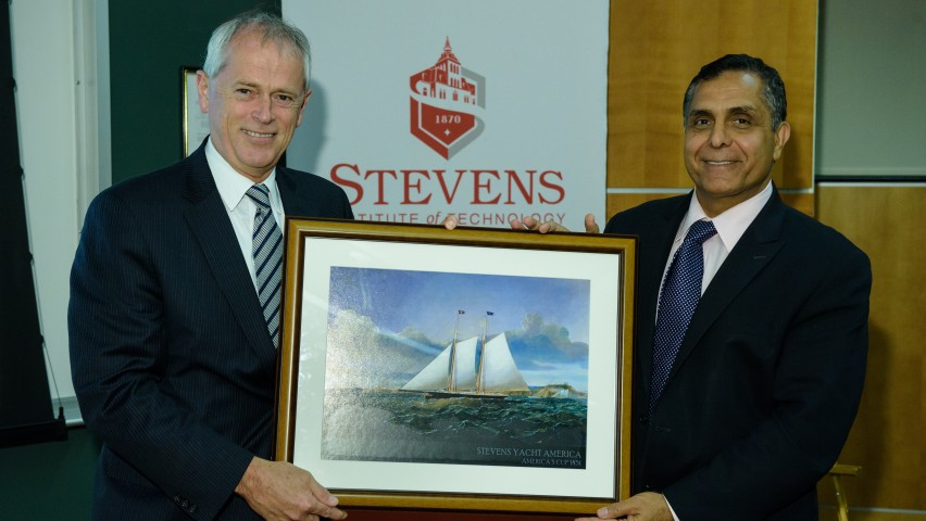 Penn State Provost Nicholas P. Jones, left, receives a framed picture of the yacht America from Stevens Vice Provost of Research Innovation and Entrepreneurship Mo Dehghani.