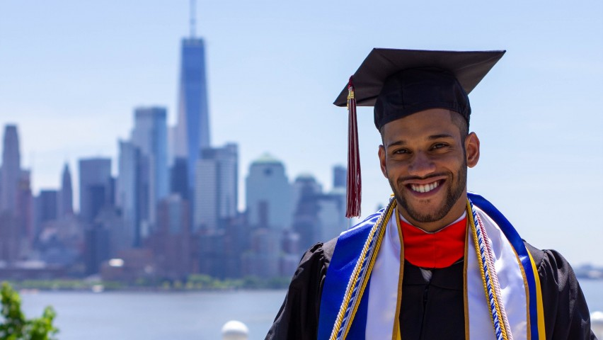 Jose Angeles-Ovalles, wearing his cap and gown, standing on Castle Point with Manhattan in the background on Commencement Day