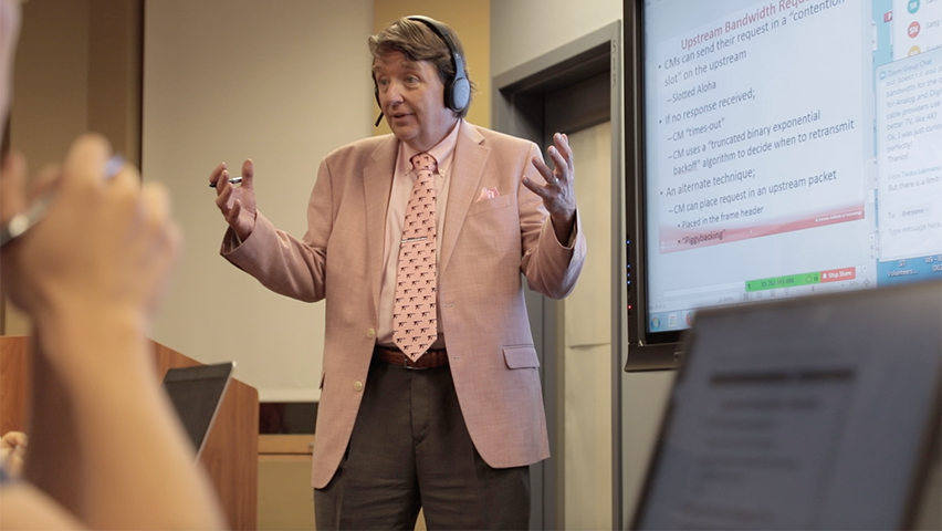 Kevin Ryan teaching in front of a screen in a hybrid classroom.