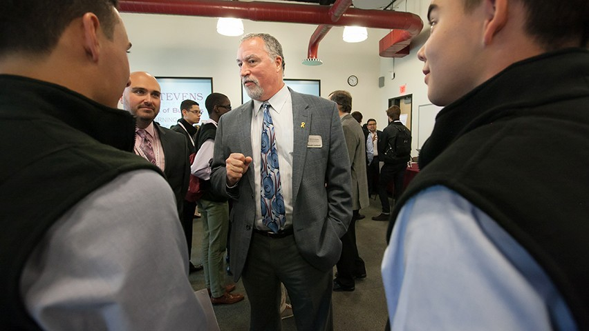 Dr. Don Lombardi surrounded by a group of students at the Stevens campus.