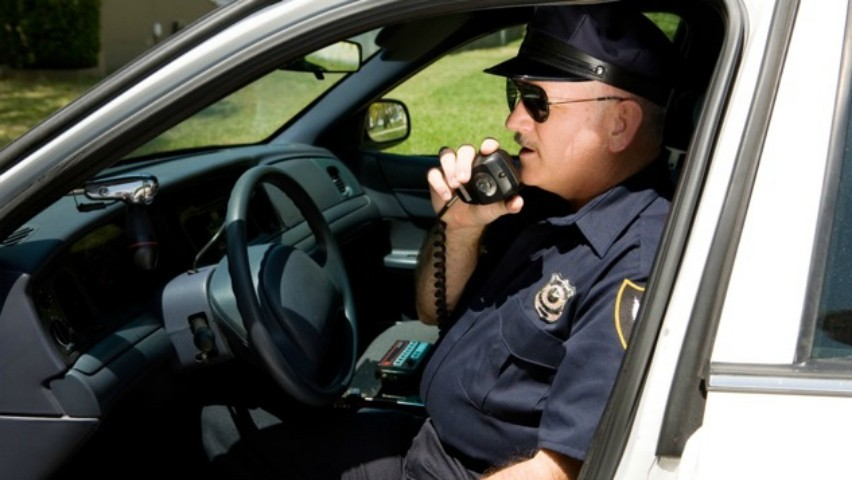 image of policeman talking on radio in police car
