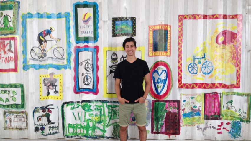 Ryan Bertani standing in front of a mural of bike motifs
