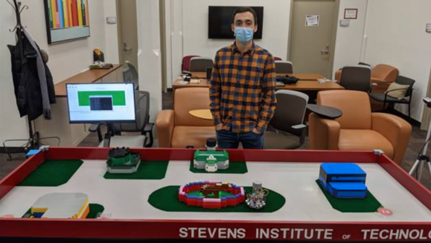 photo of student in front of Stevens campus simulation