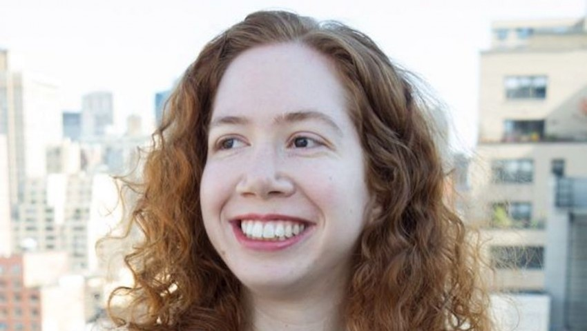 Picture of Samantha Kleinberg in black short-sleeved shirt. She is white with red hair and she is smiling.