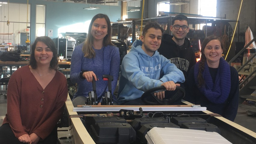 From left to right: Stevens' Solar Splash team members Victoria Davis '19, Melanie Valentin '19, Matthew Colacino '19, Justin Sitler '19 and Meghan Hand '19 pose around the competition boat inside the Griffith Building near Stevens campus
