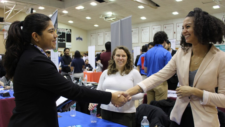 Female student on the left shakes hands with a female recruiter on the right