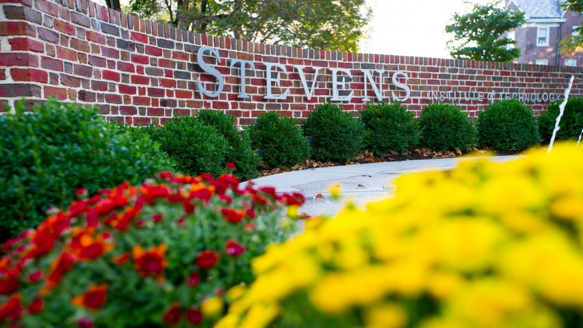 Stevens Institute of Technology signage on a brick wall in front of a fountain