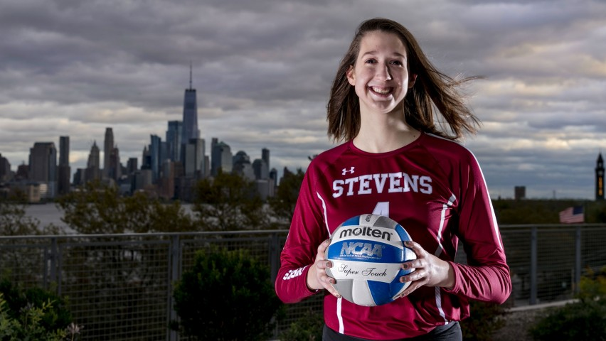 Student Shelby Stewart posing with volleyball in front of New York City skyline