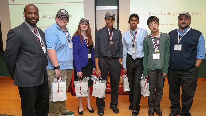 Newark High School students and advisors celebrate a hard-won victory at Trading Day.