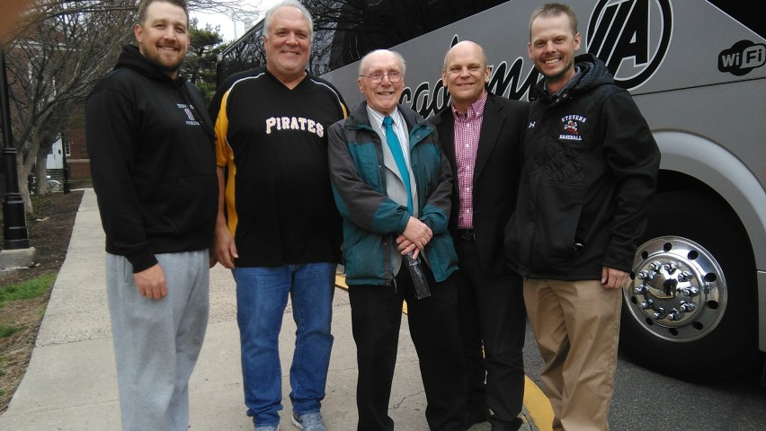 Five white men stand outside a bus