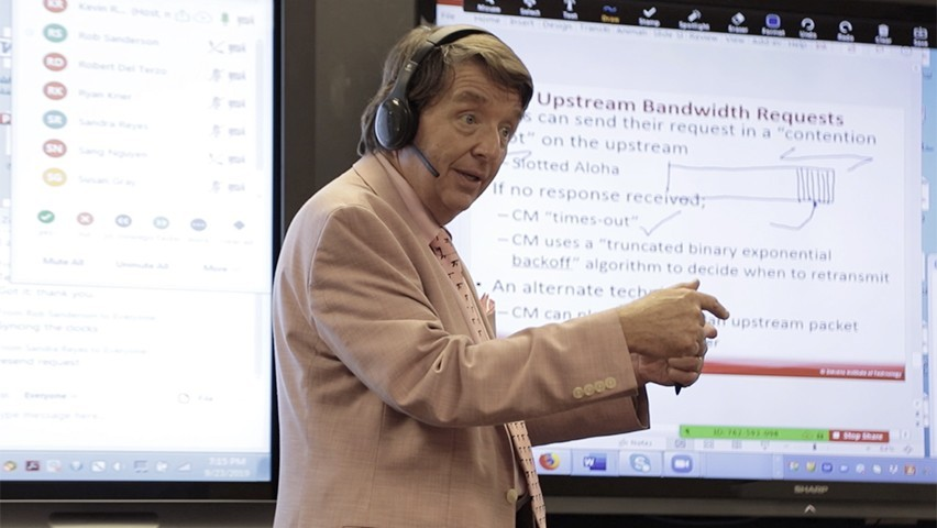A professor talks to a physical and online class through a headset. Course materials and discussion are projected in the back.