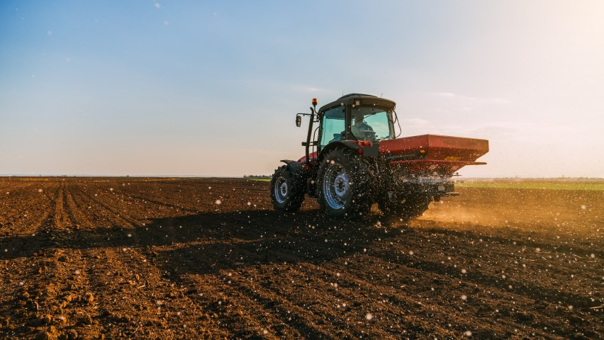 A red tractor fertilizing cropland under a blue sky