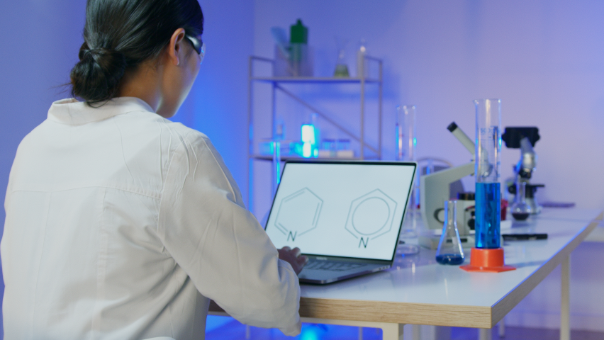 Scientist working at computer with a chemical formula on the screen