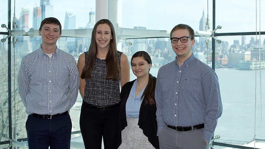 Four students, two men and two women, in a conference room with thw New York City skyline behind them.