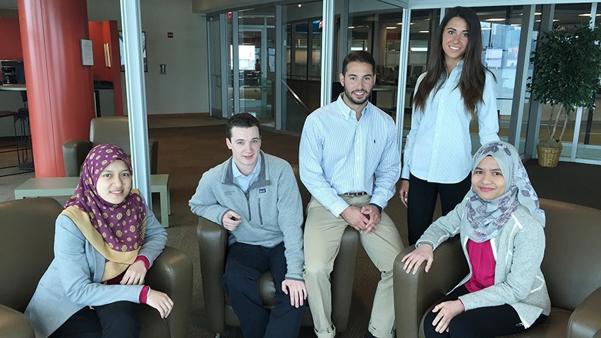 Students developing Stevens Connect pose outside the high-tech finance lab in the Babbio Center at Stevens.