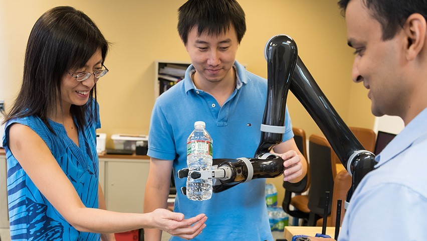 Yi Guo and Ph.D. students Chao Jiang and Muhammad Fahad work with a robotic arm. CREDIT: Kat Kendon