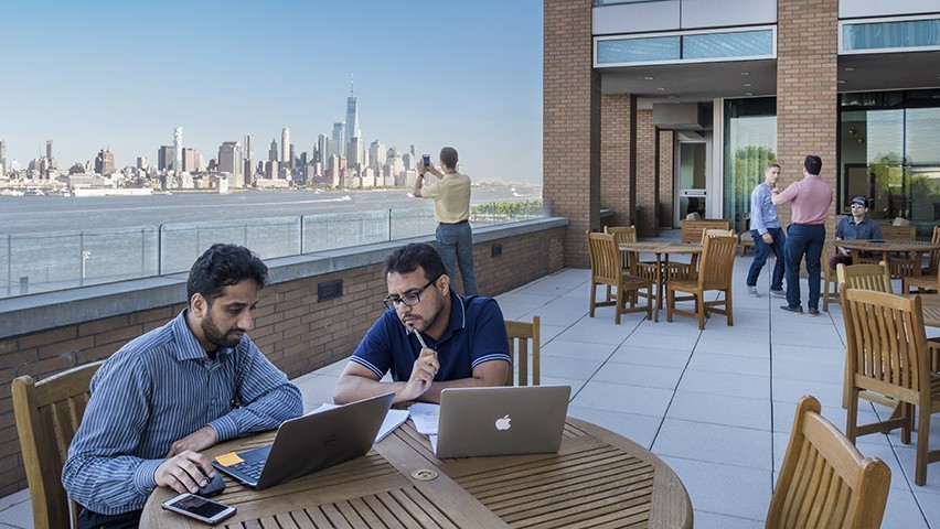 Groups of students working on a patio overlooking the lower Manhattan skyline. Two male students look at laptops in the foreground.