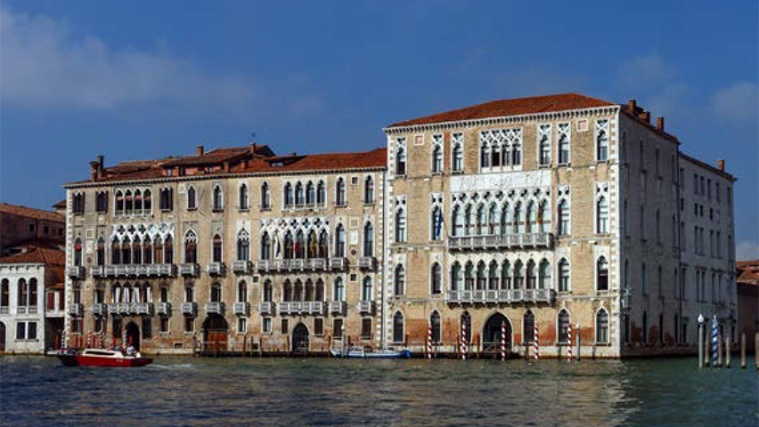 A building on the Ca' Foscari University of Venice campus. A canal and riverboat are visible in the foreground.