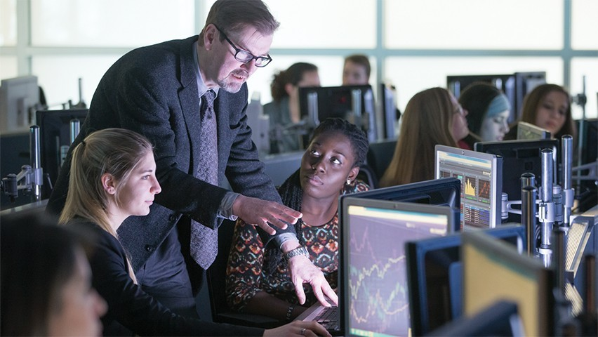 A professor walks two female students through a lesson on a Bloomberg terminal.
