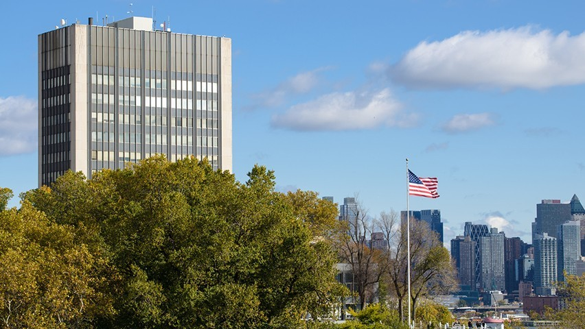 The Howe Center of the Stevens campus at the foreground, with an American flag visible, before the midtown Manhattan skyline.
