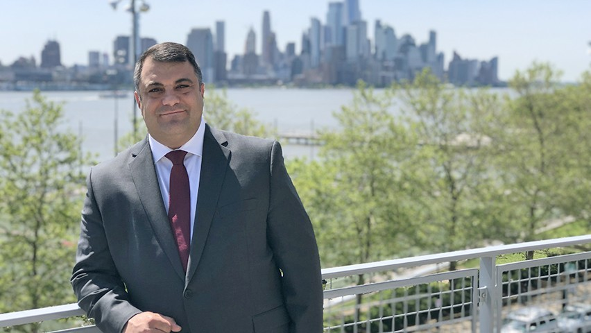 Chris Colla, in a gray suit and red tie, outside the Babbio Center with the New York City skyline behind him.