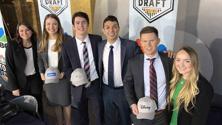 The six Stevens students holding the baseball caps with the company logos of their picks.