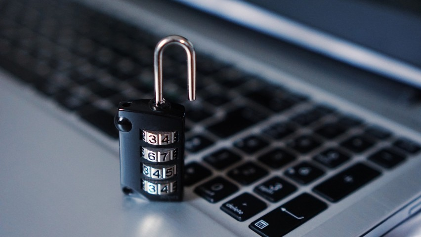 A stock image of an open lock in front a laptop keyboard.