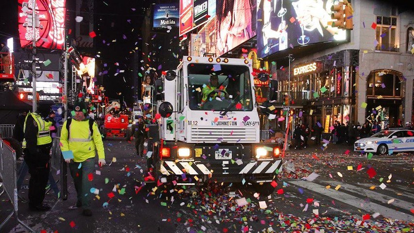 A sanitation truck collects garbage in Times Square after the crowds leave early on New Year's Day.