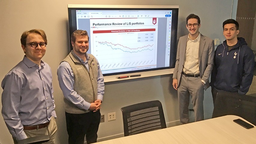 Four students show the dashboard they created while standing in a conference room at the high-tech Hanlon Lab.