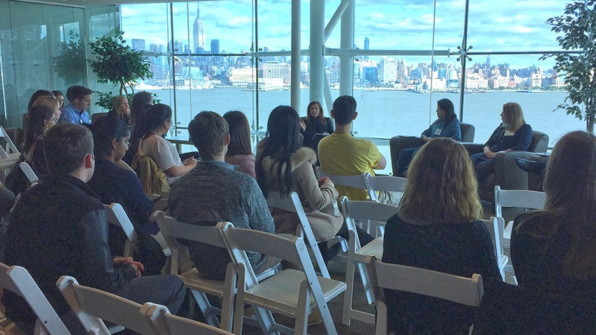 Panelists address a room packed with students in the Babbio Center at Stevens. The New York skyline is visible in the background.