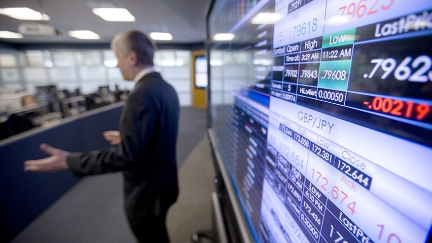 Screens in the Hanlon Lab showcase currency pricing data as a professor, dressed in a dark suit, gestures to the class.