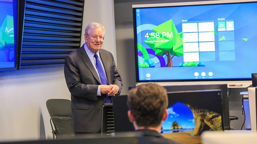 Steve Forbes talks to students in the Hanlon Lab. A number of screens and Bloomberg terminals can be seen.