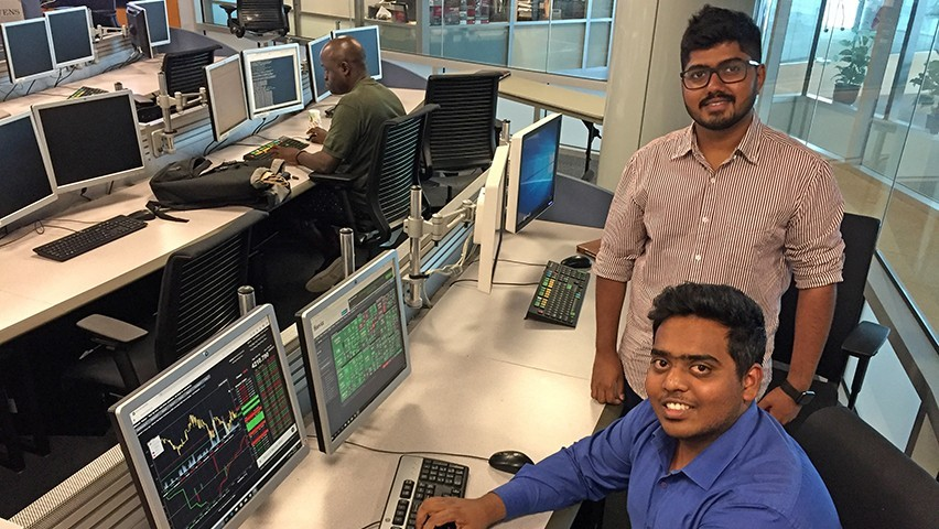 Vishnu Pillai, in a striped shirt, stands over Akshay Kumar Vikram, in a blue shirt, as he pulls up some data on a Bloomberg terminal at one of the high-tech workstations in a Stevens lab.