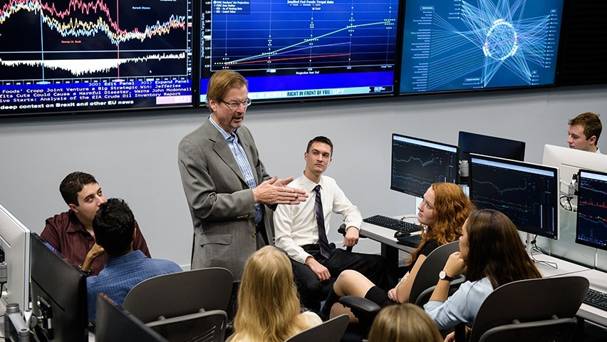 A professor teaches a class in the Hanlon Lab, with several screens behind him showing live financial market data.