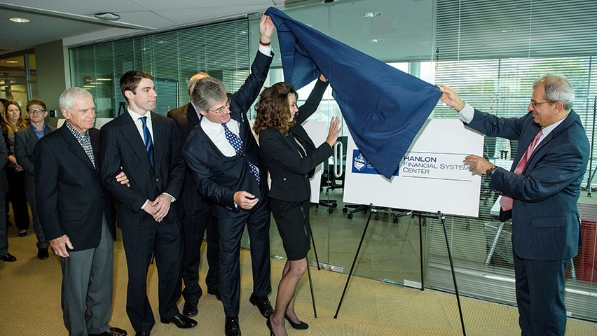 The Hanlon family unveils the logo and signage for the Hanlon Financial Systems Center during a dedication ceremony.