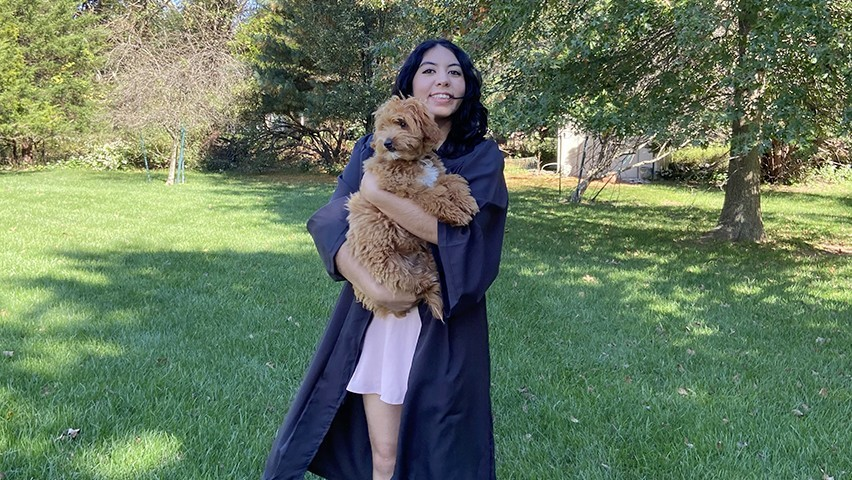 A females student poses in her backyard in graduation regalia while holding her dog.