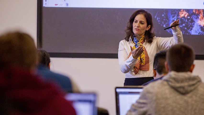 Dr. Joelle Saad-Lessler teaching a class at Stevens in front of a digital screen.